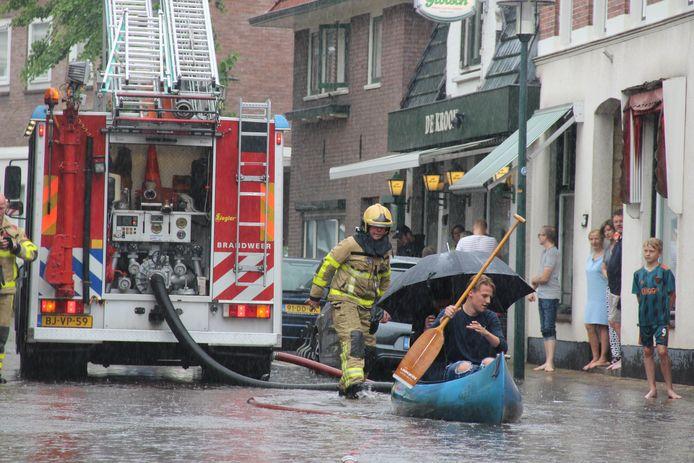 In Groenlo is zondag veel regen gevallen. In deze straat kan men daarom kanoën.
