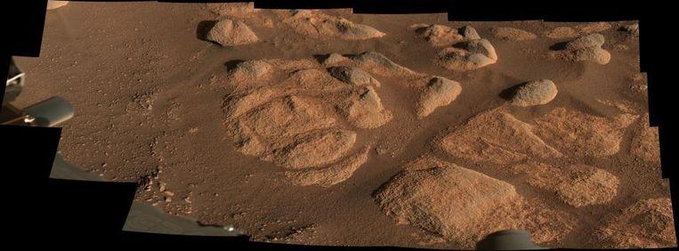 Dit beeld werd gemaakt uit 21 aparte foto's die de Marsrover nam van de bodem van Mars. De kleur benadert de echte kleur die te zien is op onze buurplaneet. Om een idee te geven van de schaal: de grootste rots die een schaduw werpt rechtsboven in beeld is ongeveer 27 centimeter groot. Het volledige beeld heeft een doorsnee van drie meter. Beeld NASA/JPL-Caltech/ASU/MSSS