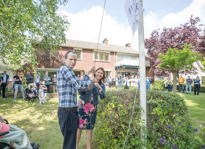 Bewoner Menno van Dommelen en burgemeester José van Egmond hijsen de vlag bij het nieuwe huis van Salcha Zorg.