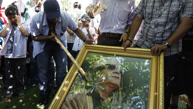 Demonstranten slaan een poster stuk van Muammar Kaddafi. Beeld reuters