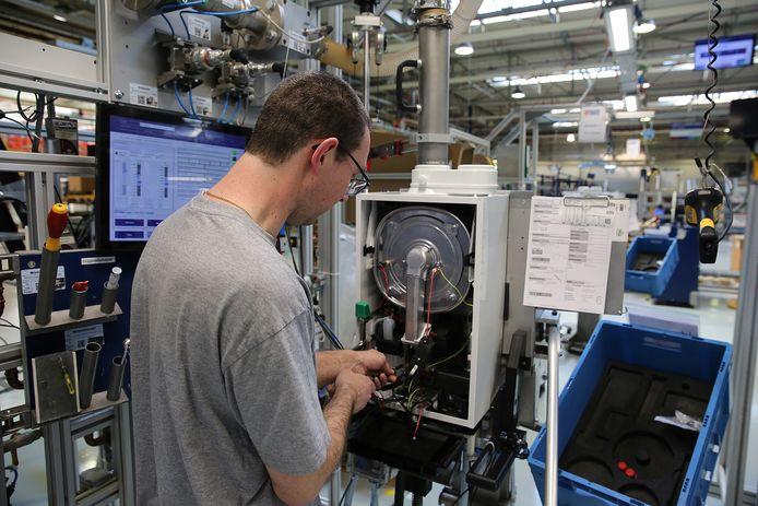 Een Nefit-medewerker is in de productiehal in de weer met een cv-ketel.