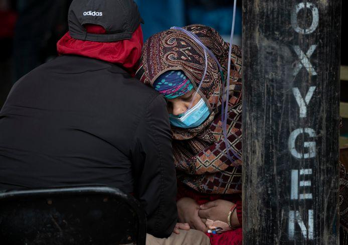 Een coronapatiënt krijgt zuurstof toegediend buiten aan een ziekenhuis in Kathmandu, Nepal. (AP Photo/Niranjan Shrestha)
