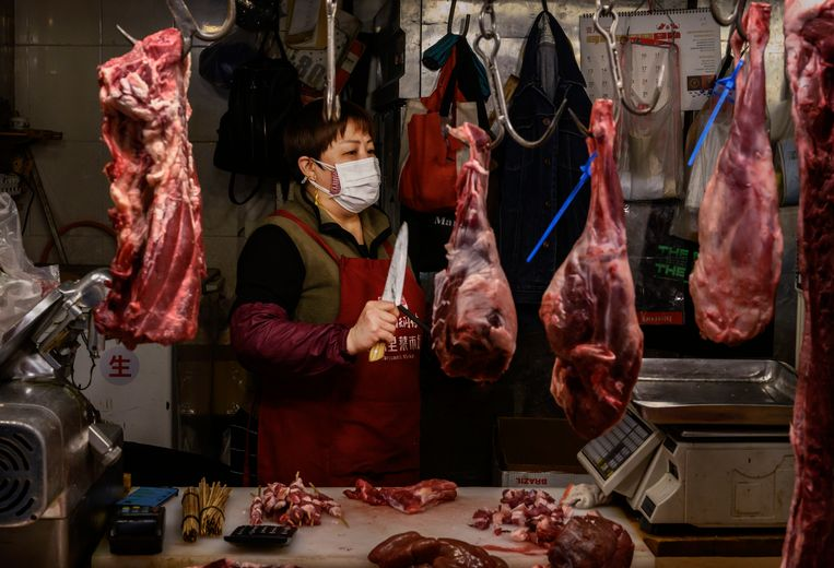 Een beenhouwer op de markt in Peking.