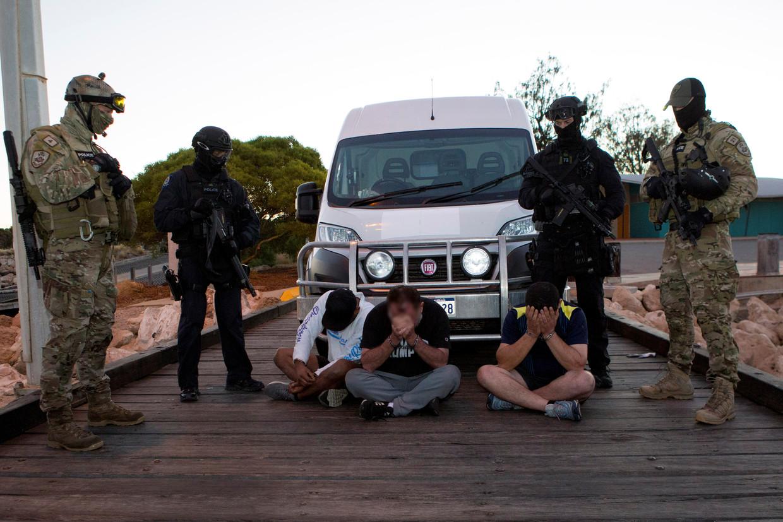 Politieagenten bewaken drie mannen die worden verdachten van meth-smokkel in het stadje Geraldton aan de westkust van Australië.