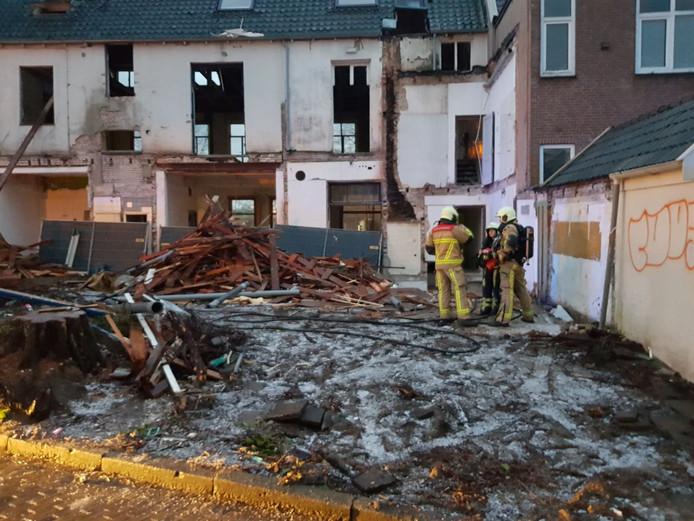 De brandweer inventariseert de schade in voormalig hotel De Kroon. De brand woedde binnen. De puinhoop buiten is geen gevolg van de brand.