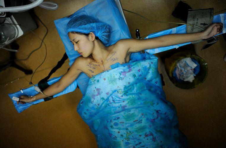 Een 21-jarige vrouw krijgt een borstimplantaat in de Chinese plaats Hefei.  Beeld Archief Reuters