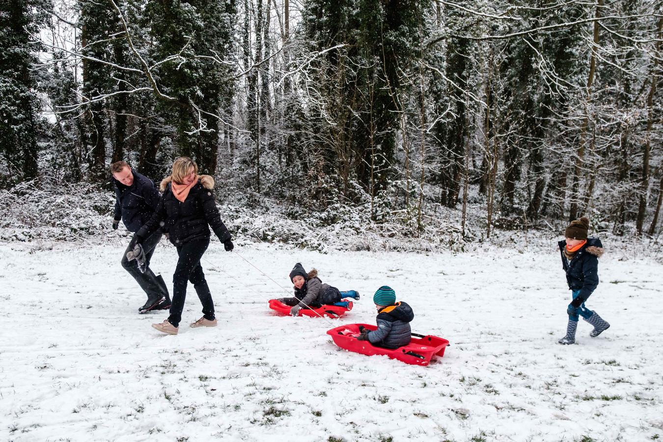 Aaron, Julian en Nicola spelen met hun ouders in de sneeuw.