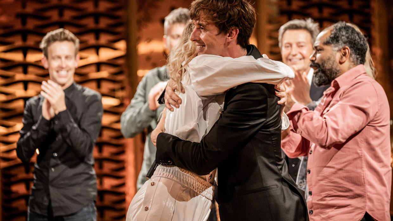 Emma Bale knuffelt Bert Ostyn. In de achtergrond vlnr: Jonas Van Geel, Tourist LeMC, Willy Sommers, Ronny Mosuse Beeld VTM
