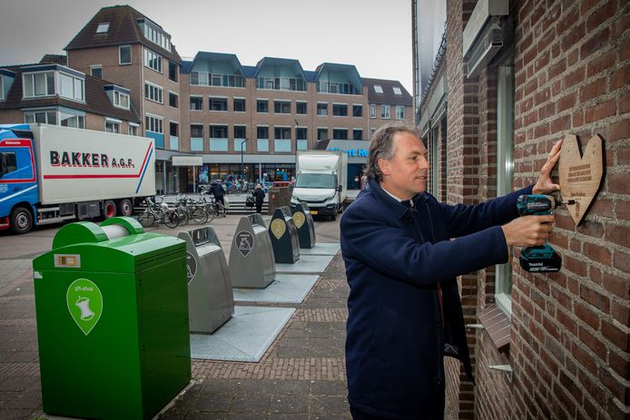 Wethouder Geert Gerrits schroeft het bordje op de muur van het oude gemeentehuis in Wijchen. Daarmee is het gebouw officieel een 'donorgebouw'.