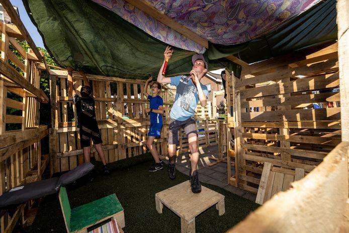 Jongeren uit de buurt bouwen zelf op de parkeerplaats een hut