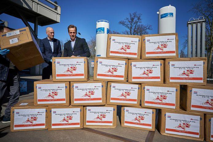 Minister Hugo de Jonge neemt de eerste dozen mondkapjes in ontvangst van Steven Cai (Huawei). Het telecommunicatiebedrijf doneert 800.000 mondmaskers. Zondag arriveerden de eerste 200.000 exemplaren.