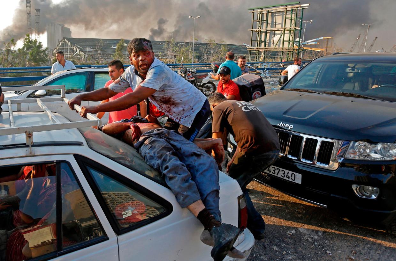 Omstanders helpen een zwaargewonde man.De ravage in Beiroet was enorm: minstens 135 mensen lieten het leven, onder wie twee Belgen.  Beeld AFP