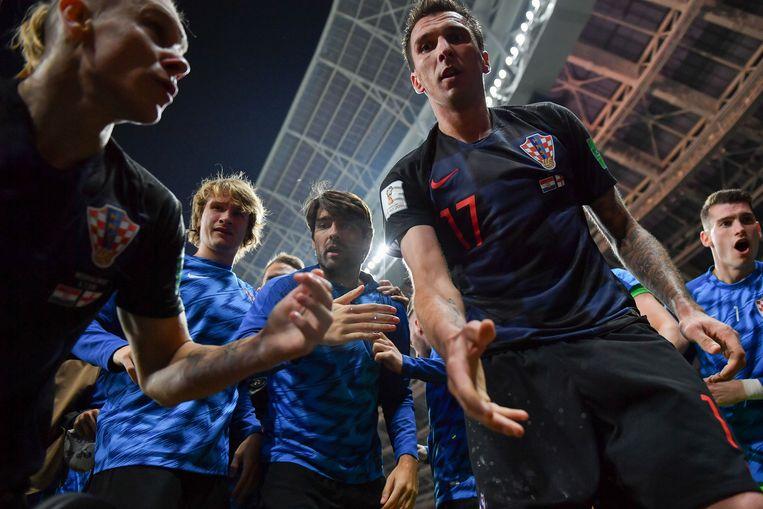 Kroatië-spits Mario Mandzukic wil fotograaf Yuri Cortez helpen opstaan tijdens de halve finale. Beeld AFP