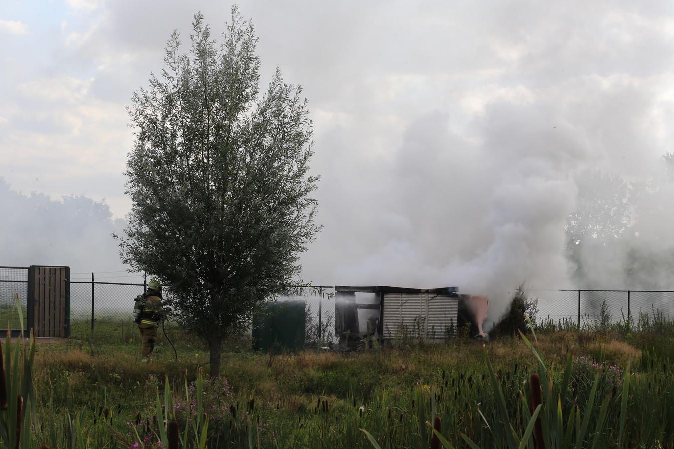 De brandweer blust de brand in het stroomhuisje in Vlijmen.