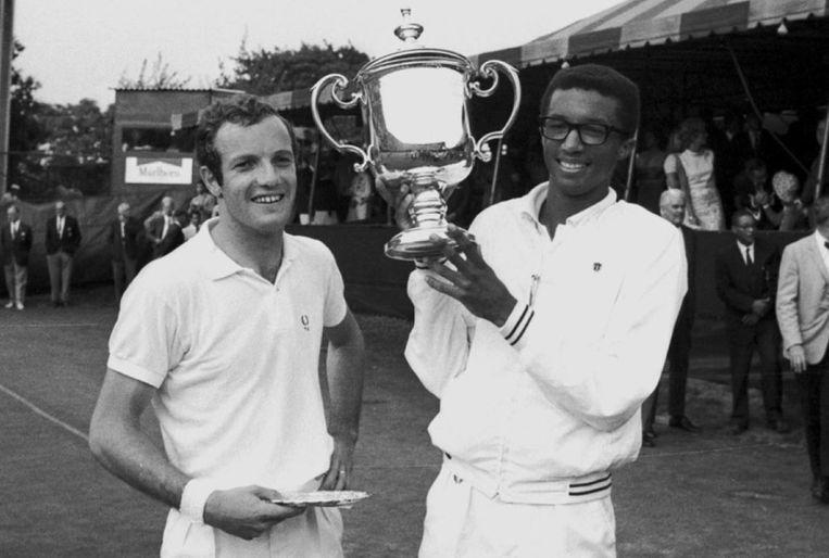 Arthur Ashe houdt zijn prijs omhoog nadat hij Tom Okker heeft verslagen op de U.S. Open in Forrest Hills. Ashe speelde als eerste Afro-Amerikaanse tennisspeler voor het Davis Cup team en won ook als eerste Afro-Amerikaanse speler de U.S. Open en Wimbledon.  Beeld Walter Kelleher/Getty Images