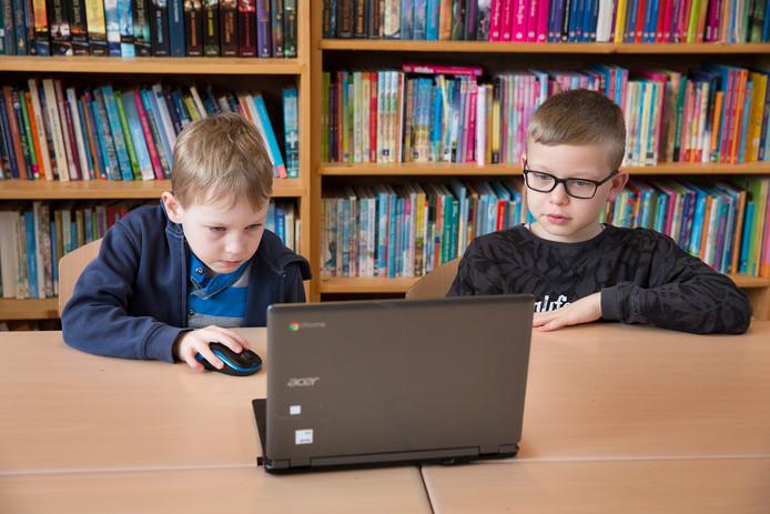 Luc (rechts) uit groep 8 helpt Jitse (groep 3) bij de extra leesles.