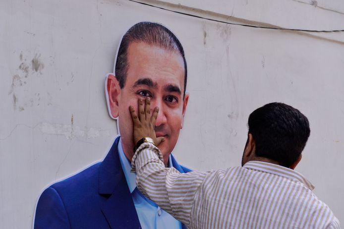 Archiefbeeld uit 2018: een betoger houdt zijn hand op het gelaat (van een afbeelding) van Nirav Modi nadat bekend werd dat de diamantiar een rol zou hebben gespeeld in een fraude van 1,5 miljard euro met de Punjab National Bank.