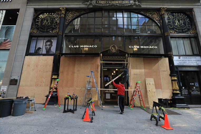 Verschillende winkels en bankkantoren hebben de voorbije dagen hun vitrines al preventief dichtgetimmerd uit vrees door rellen en plunderingen.  Beeld Photo News