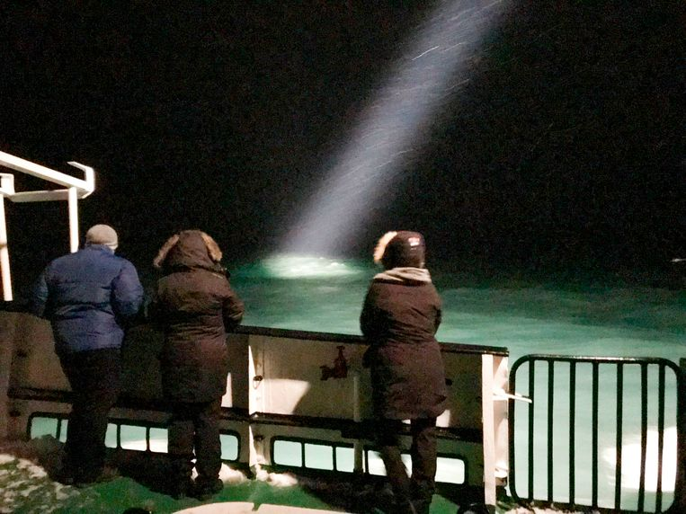 Toeristen slaan vanop een schip de zoektocht naar de helikopter gade. Beeld afp