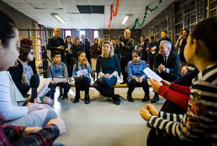 Minister Kajsa Ollongren van Binnenlandse Zaken sprak in 2018 met leerlingen in Rotterdam-Zuid, toen zij bekendmaakte met de gemeente tientallen miljoenen extra te steken in het basisonderwijs. Volgens Marco Pastors (rechts op de bank) vallen de resultaten tegen vanwege het lerarentekort.