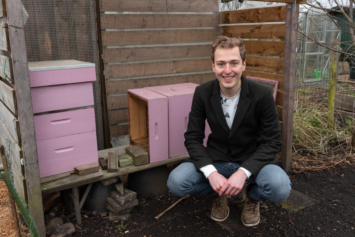 Marc Hilhorst in zijn volkstuin bij enkele bijenkasten. De bijen bestuiven zijn bloemenperk.