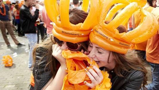 Feestvierders hebben lol tijdens het opblazen van oranje kronen tijdens het feestje in Breda