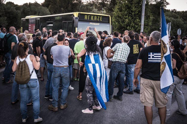 Een bus met migranten wordt door inwoners de weg versperd. Beeld Nicola Zolin