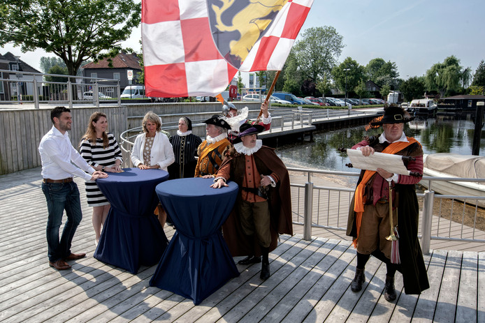 De stadsomroeper brengt het nieuws van de app. Schepenen Petra Lepolder van Steenbergen (tweede van links) en Yvonne Kammeijer van Bergen op Zoom (naast haar) luisteren toe.