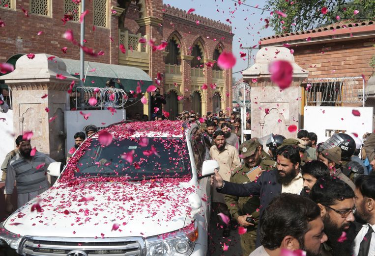 De wagen van Hafiz Saeed wordt door aanhangers bedolven onder rozenblaadjes na afloop van een rechtbankzitting in Lahore, november 2017. Saeed werd woensdag opgepakt op verdenking van het financieren van terroristische organisaties.  Beeld AP