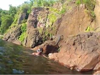 Krokodil springt aan waterval recht op zwemmende toerist