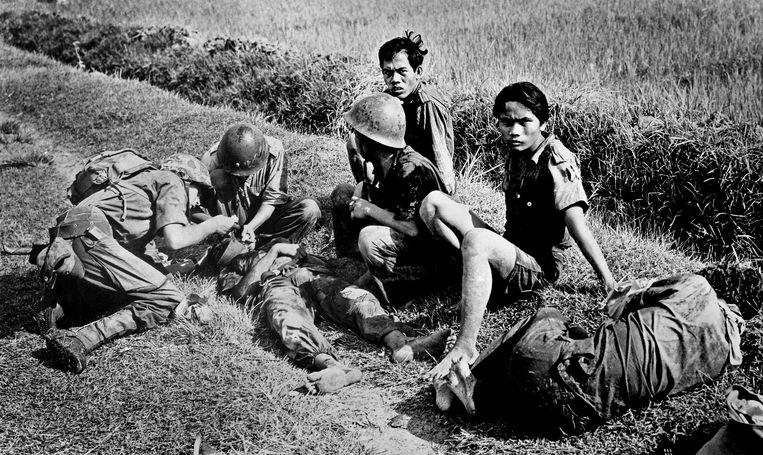 Ziekenverplegers van de mariniers verlenen eerste hulp aan gewonde pemoeda's na een zuiveringsactie in de buurt van Soerabaja. Beeld ANP