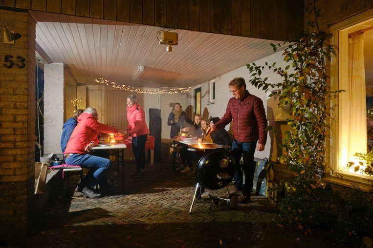 Een huiskerk in Drachten, december vorig jaar. Wegens corona kwam men samen onder de carport, met barbecue, bijbels en kerstboom met lichtjes.  Beeld Sjaak Verboom
