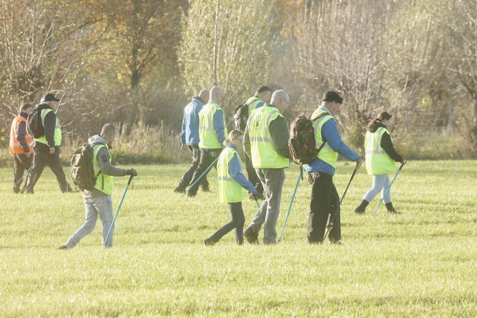 Leden van het Veteranen Search Team doorzoeken een weiland aan de Amerongerwetering.