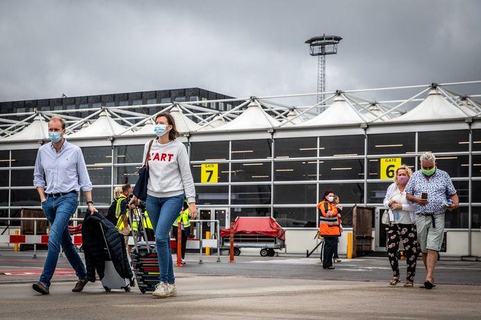 Reizigers met mondkapjes op Rotterdam The Hague Airport.