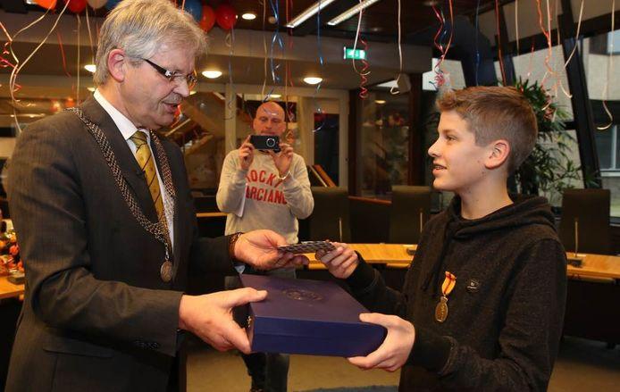 Ruben krijgt de onderscheiding uit handen van burgemeester Jos Penninx. Foto: Ronny te Wechel