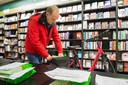 Medewerker Theo Heeren van de Etten-Leurse Readshop stopt bestelde boeken in de fietstas. Daarna levert hij ze af.