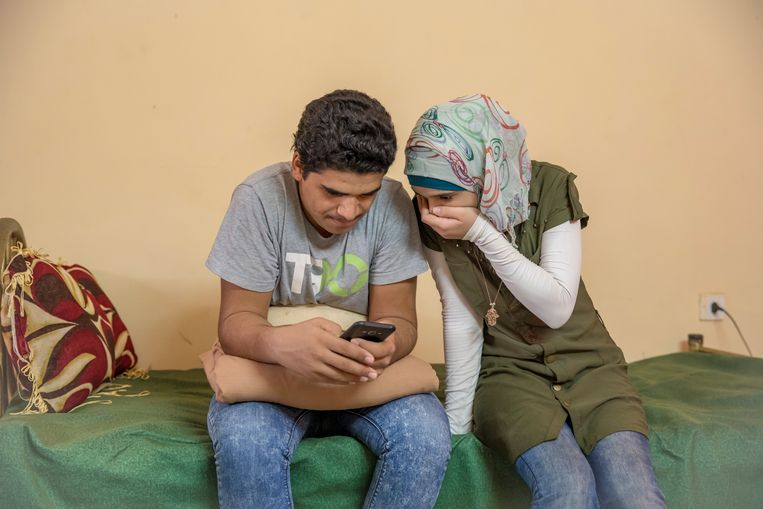 De twee kinderen van vader Yasser die het niet gelukt zijn om naar Duitsland te vluchten, wonen nu in een eenvoudig appartement in Khartoum. Via de mobiele telefoon hebben ze dagelijks contact met hun moeder en broertjes en zusje in Duitsland, of kijken ze naar beeldmateriaal over de oorlog in Syrië. Beeld Sven Torfinn