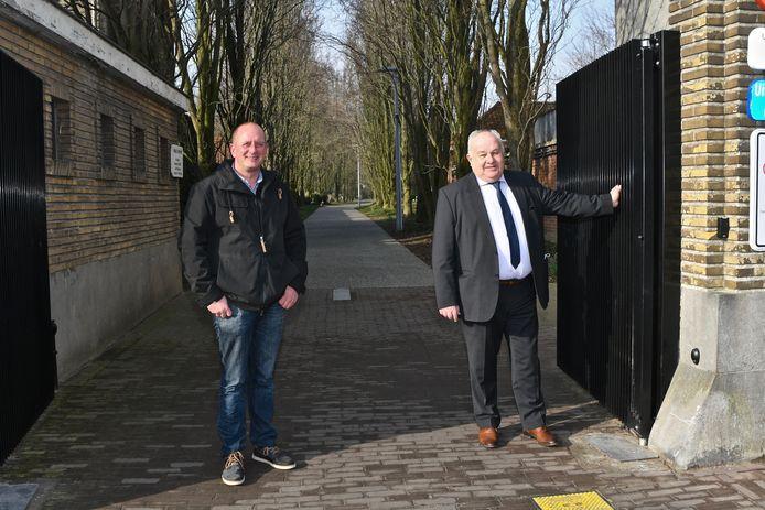 Schepen Marc Vanwalleghem en begraafplaatsbeheerder Wim Vercruysse stellen de nieuwe  automatische poorten voor.