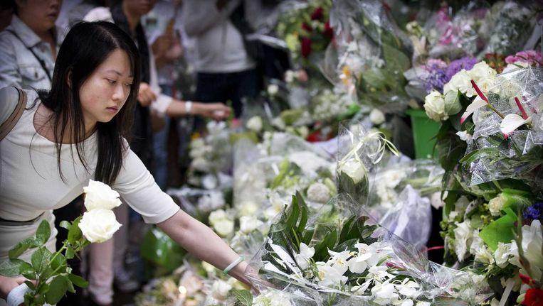 Treurende Rotterdammers leggen bloemen bij het restaurant na een stille tocht voor het omgekomen echtpaar Jenny Loh en Popo Fan, eigenaars van een populair restaurant. Samen met de moeder van Jenny zaten zij aan boord van de neergestorte vlucht MH17 van Malaysia Airlines. Beeld anp