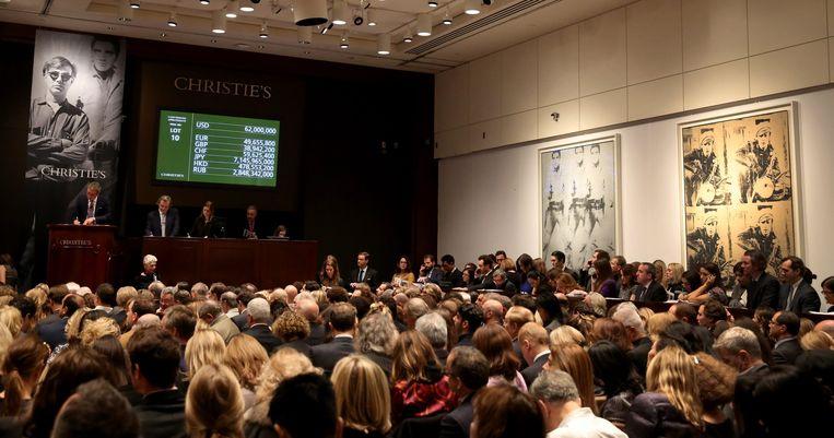 De veiling bij Christie's in New York waar twee kunstwerken van Andy Warhol zo'n 151 miljoen dollar opbrachten. Beeld epa