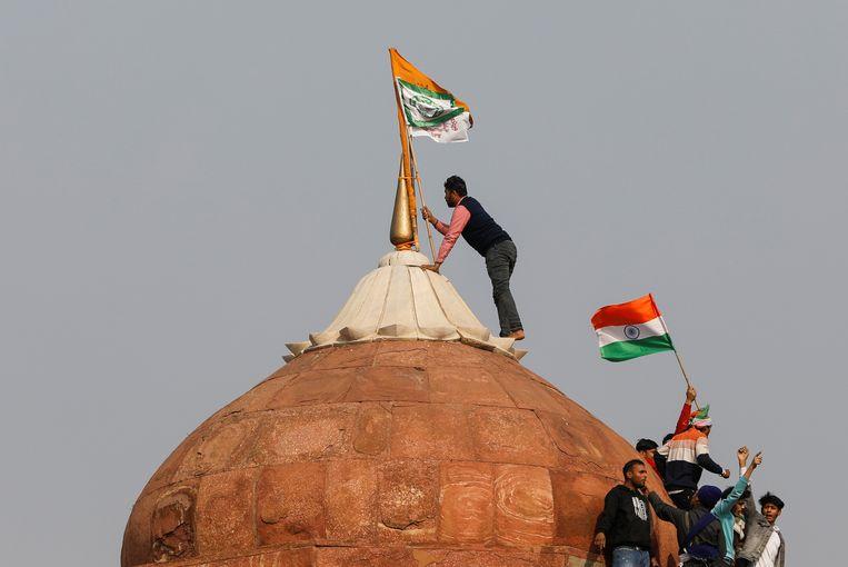 Een boer hangt een vlag op de top van het Rode Fort.  Beeld Reuters