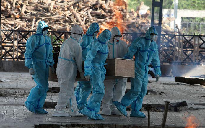 Gezondheidswerkers dragen het stoffelijk overschot van een coronadode naar een crematorium in India