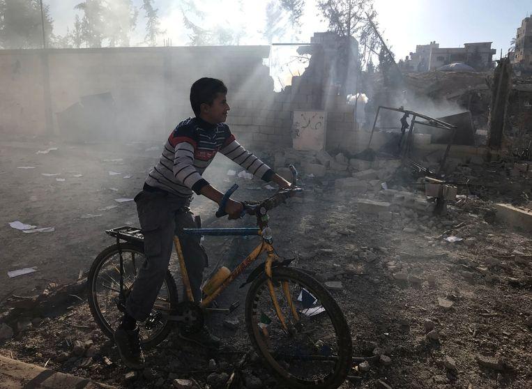 Een Palestijnse jongen fietst voorbij de nasmeulende restanten van een bominslag Beeld REUTERS