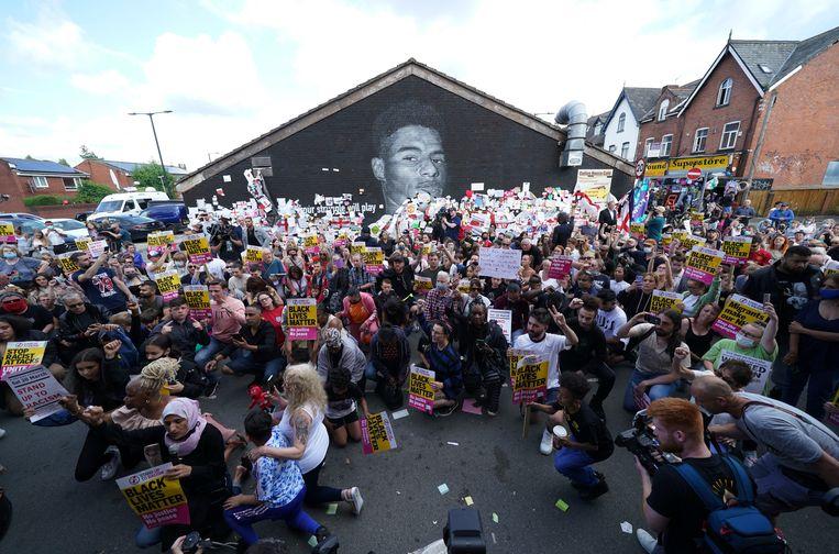 Mensen protesteren tegen racisme bij een muurschildering van voetbalspeler Marcus Rashford in Manchester.  Beeld AP