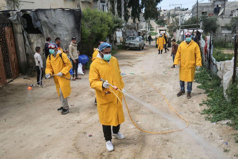 Palestijnse vrijwilligers ontsmetten een straat in de stad Rafah, op de grens van de Gazastrook en Egypte, om de verspreiding van het coronavirus tegen te gaan.  Beeld AFP
