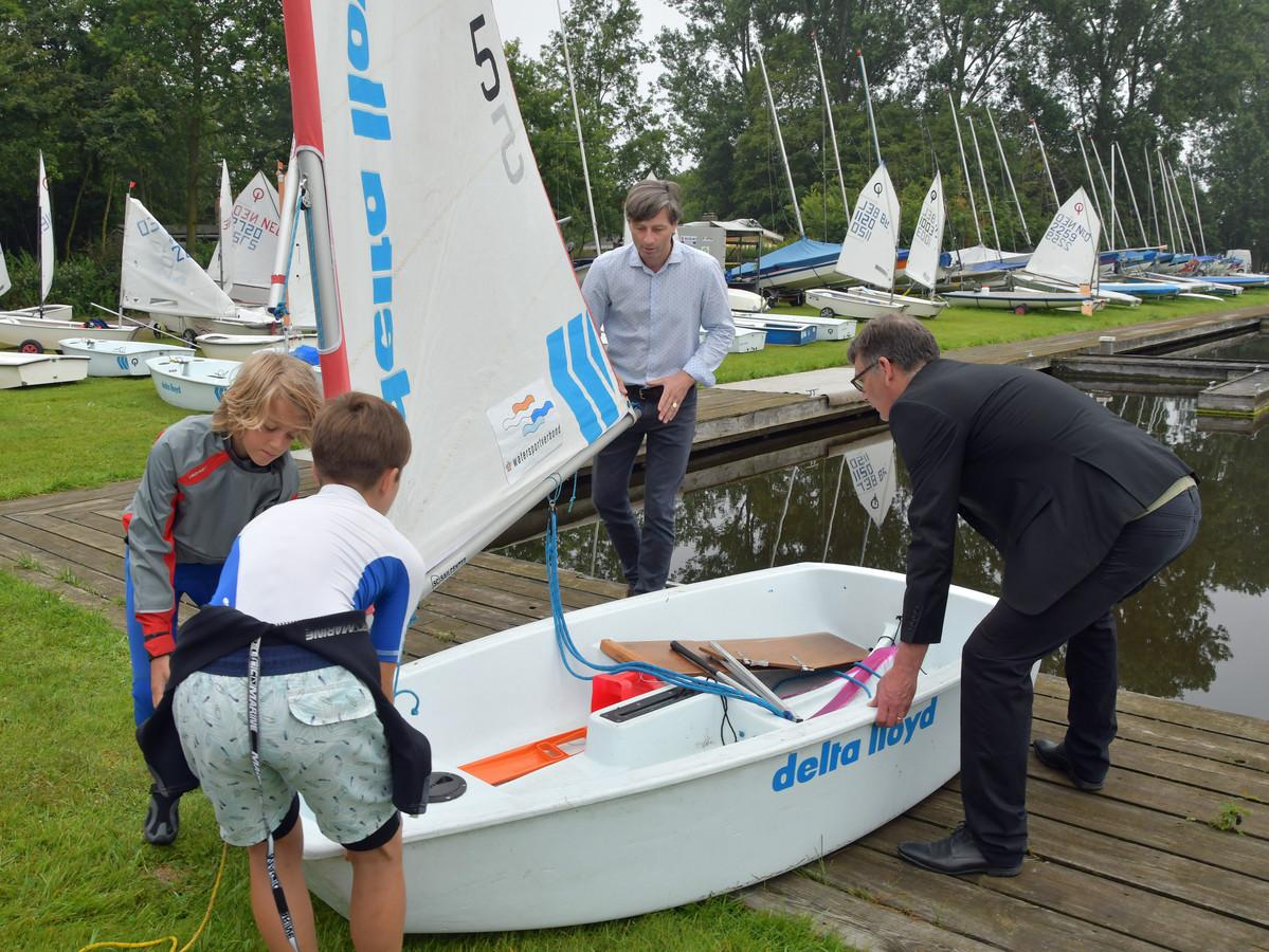 De zeilweek van vereniging Vremdijck in de Braakman gaat van start. Wethouder Frank van Hulle (r) laat samen met voorzitter Mark Willems, Bob van der Donk (korte broek) en Vince Moring de eerste optimist te water.