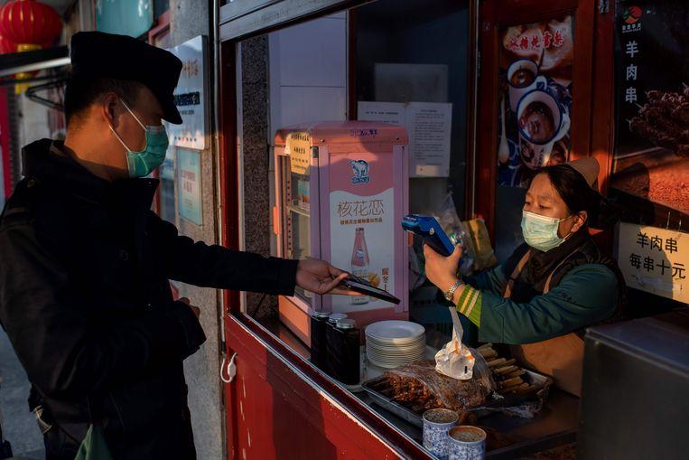 Een klant bij een Chinees winkeltje betaalt met zijn mobiele telefoon.  Beeld AFP