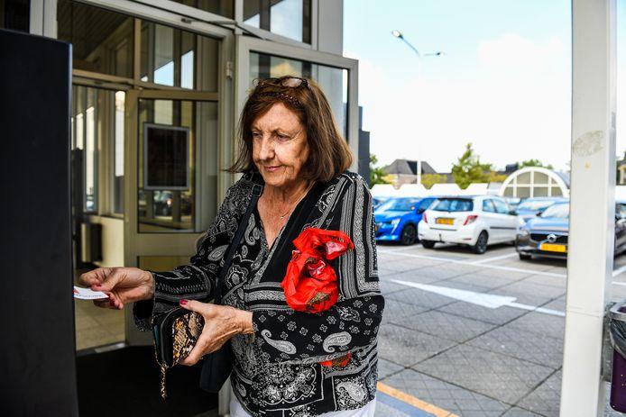 Een vrouw koopt een parkeerkaartje op het dak van de Aarhof