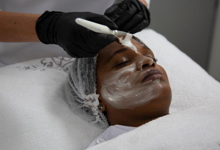 Een huidbleekmasker wordt op het gezicht van een vrouw aangebracht. Beeld AP