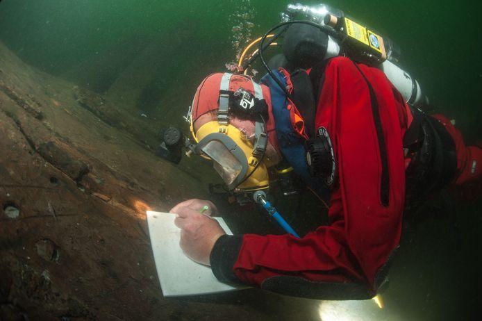 Een onderwaterarcheoloog bestudeert de constructie van het 17de-eeuwse houten scheepswrak Oostvoornsemeer (OVM) 14, waarvan de resten op bijna 30 meter diepte meer dan 3 meter boven de bodem uitsteken.